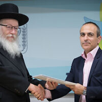 Then Deputy Health Minister Yaakov Litzman, left, shakes hands with Ronni Gamzu during a press conference at the Health Ministry in Jerusalem on January 3, 2019. (Noam Revkin Fenton/Flash90)