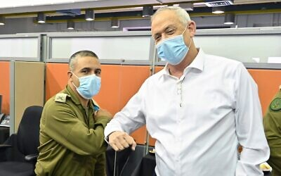 Defense Minister Benny Gantz (right) bumps elbows with Brig. Gen. Nissan Davidi, who was tasked with leading the military's Coronavirus Command on August 4, 2020. (Ariel Hermoni/Defense Ministry)