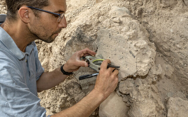 TAU PhD student Yoav Vaknin takes measurements of a floor that collapsed during the 586 BCE destruction of Jerusalem by the Babylonians at excavations in the City of David Park in Jerusalem. (Shai Halevi/Israel Antiquities Authority)