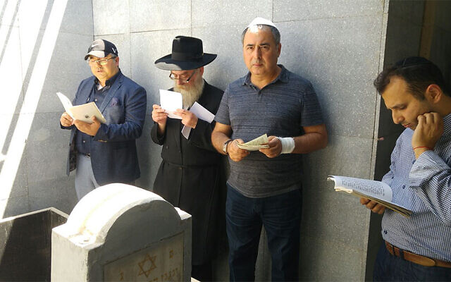 Men pray around the grave site of Levi Yitzchak Schneerson in Almaty, Kazakhstan in 2016. (Courtesy of Chabad Kazakhstan via JTA)