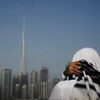 A man sporting a Jewish 'tallit' looks out over the Dubai skyline in the United Arab Emirates (video screenshot)