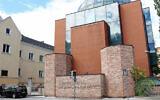 A man walks past the defaced facade of the synagogue of Graz, Austria, on August 19, 2020. (Christian Jauschowetz via JTA)