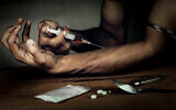 A man with a syringe used to inject heroin (iStock)