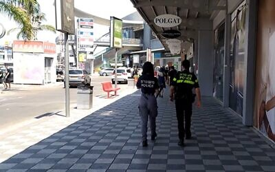 Police officers at the Bilu shopping center after stores opened in defiance of regulations, August 1, 2020 (Screen grab/Channel 12 news)