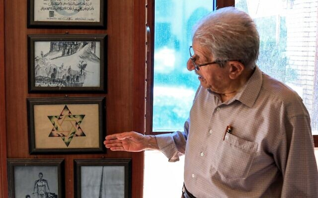 Omar Farhadi, an elderly Iraqi Kurd points to a frame showing a stylized hexagram, or a Star of David, hanging in a room dedicated to famous Jewish Kurdish art teacher and painter Daniel Kassab, at the Museum of Education in Erbil's oldest primary school, in the capital of the autonomous Kurdish region of northern Iraq, on July 5, 2020. (SAFIN HAMED / AFP)