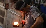 A glassblower forms glass at factory, which is recycling the broken glass as a result of the Beirut explosion, in the northern Lebanese port city of Tripoli on August 25, 2020 (JOSEPH EID / AFP)