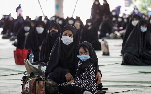 """Shiite Muslim worshipers, mask-clad due to the COVID-19 coronavirus pandemic, attend the """"Tasua"""" (ninth day) mourning ritual to commemorate the martyrdom of Prophet Mohammad's grandson Imam Hussein during the Islamic month of Muharram ahead of Ashura, at the Tehran University campus in Iran's capital on August 29, 2020. (AFP)"""