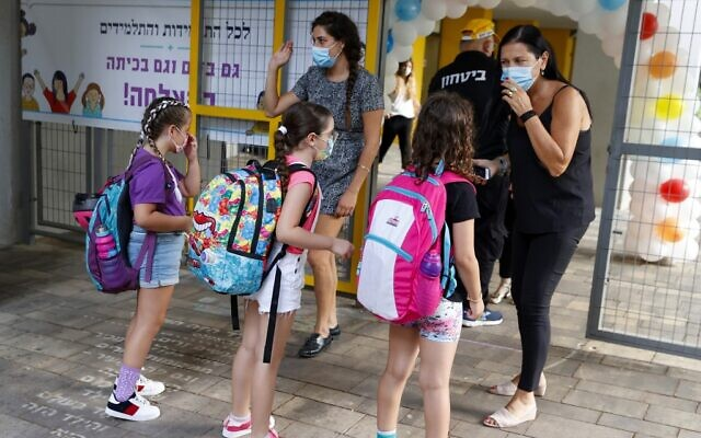 Israeli school teachers speak with students on the first day of school, during the coronavirus pandemic, in Tel Aviv on September 1, 2020. (JACK GUEZ / AFP)