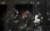 Palestinian man Omar al-Hazeen (R) reacts at his torched house where his three children were killed in a fire ignited by a candle used to light up their room during a power cut in al-Nusirat refugee camp in the central Gaza Strip on September 2, 2020. In response to the persistent arson balloon launches from the Gaza Strip, Israel has banned fishing off Gaza's coast and closed the Kerem Shalom goods crossing, cutting off deliveries of fuel to the territory's sole power plant. Power had been in short supply even before the shutdown, with consumers having access to mains electricity for only around eight hours a day. (MAHMUD HAMS / AFP)