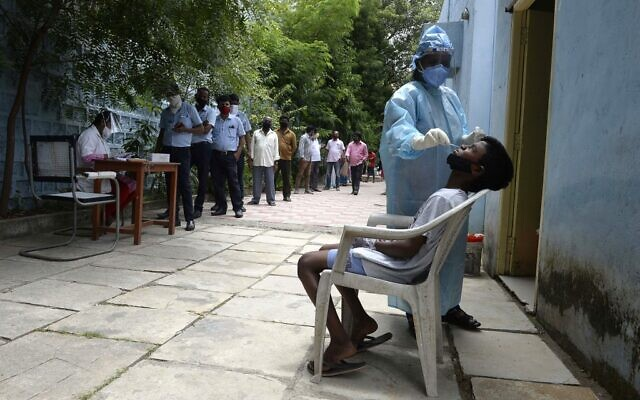Residents stand in a queue to register their names as a health worker collects a swab sample to test for the coronavirus, at a primary health center in Hyderabad on September 4, 2020. (NOAH SEELAM / AFP)