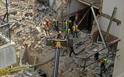Rescue workers dig through the rubble of a badly damaged building in Lebanon's capital Beirut, in search of possible survivors from the mega-blast at the adjacent port one month before; September 4, 2020. (Joseph Eid/AFP)
