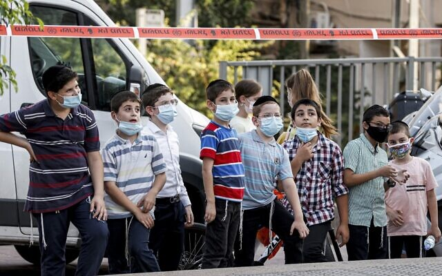 Children, mask-clad due to the COVID-19 pandemic, stand on a street in the ultra-Orthodox city of Bnei Brak on September 6, 2020. (Jack Guez/AFP)
