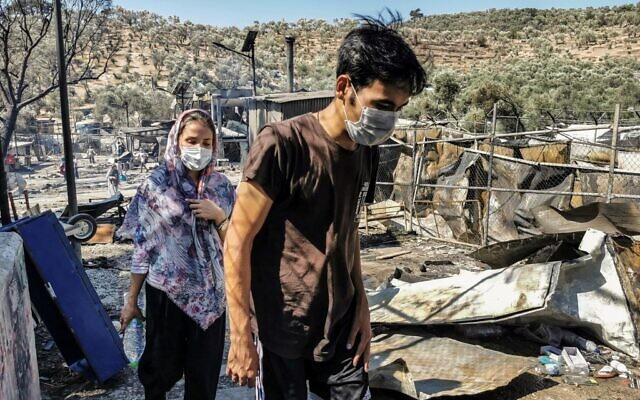 Migrants walk inside the burnt Moria Camp on the Greek island of Lesbos on September 9, 2020, after a major fire. (Anthi PAZIANOU / AFP)