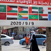 """A banner showing the flags of Arab countries and reading """"History will only glorify those loyal to Palestine"""" is seen during a rally against the UAE-Israel normalization deal, in the occupied West Bank city of Nablus on September 9, 2020. (Photo by JAAFAR ASHTIYEH / AFP)"""