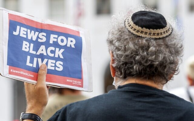 Illustrative: A man wearing a kippah holds a sign reading 'Jews for Black Lives' at the weekly Black Lives Matter 'Jackie Lacey Must Go!' protest in front of the Hall of Justice in Los Angeles, California, September 9, 2020 (VALERIE MACON / AFP)