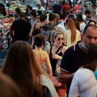 Shoppers, some wearing face masks against the coronavirus,  crowd Jerusalem's Mahane Yehuda market on September 11, 2020. (Emmanuel Dunand/AFP)