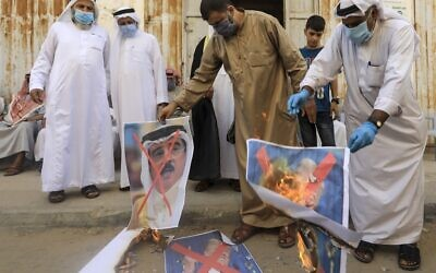 Palestinian men burn the exed-out portraits of the Bahraini king, US president and Israeli premier during a protest in Deir al-Balah, in the central Gaza Strip, on September 12, 2020. (MAHMUD HAMS / AFP)