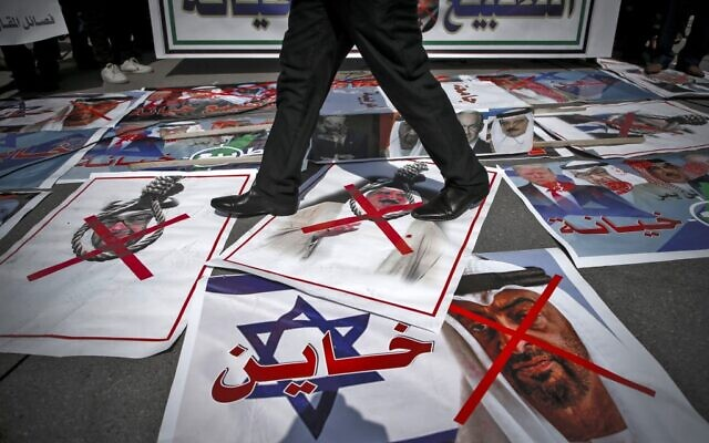 A demonstrator walks on pictures laid out on the ground depicting X-marks over the faces of Bahrain's King Hamad bin Isa al-Khalifa and Abu Dhabi Crown Prince Sheikh Mohammed bin Zayed al-Nahyan, during a protest against the United Arab Emirates' and Bahrain's decisions to normalize relations with Israel, in Gaza City on September 15, 2020. (Mohammed ABED / AFP)