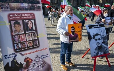 A man holds a portrait of Iranian wrestler Navid Afkari during a demonstration against his execution during a protest held on the Dam Square in Amsterdam, September 13, 2020. (Evert Elzinga/ANP/AFP)