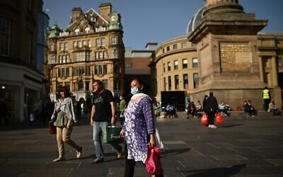 Pedestrians and shoppers, some wearing face masks due to the coronavirus pandemic, walk in Newcastle city center, northeast England, on September 17, 2020. (Oli Scarff/AFP)