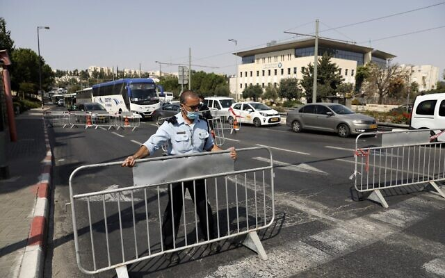 Policemen set up barriers to traffic at a checkpoint in Jerusalem on September 18, 2020, to enforce a new lockdown amid the COVID-19 pandemic (Ahmad GHARABLI / AFP)