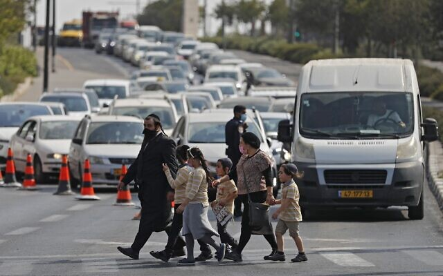 People cross a street in Jerusalem as police man a checkpoint to enforce a new lockdown amid the COVID-19 pandemic, on September 18, 2020 (Ahmad GHARABLI / AFP)