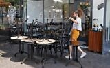 An employee puts away the furniture of a restaurant in the coastal city of Tel Aviv on September 18, 2020, ahead of a nationwide lockdown to tackle a spike in coronavirus cases. (JACK GUEZ/AFP)