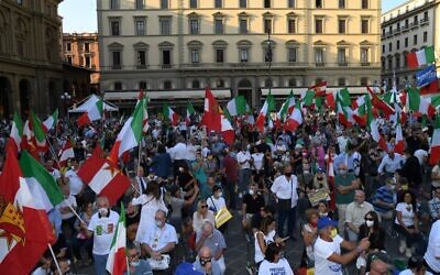 Supporters hold Italian flags during a center-right coalition rally of the Lega, Brothers of Italy and Forza Italia parties for the upcoming regional elections, on September 18, 2020, in Florence, Tuscany. (Carlo Bressan/AFP)