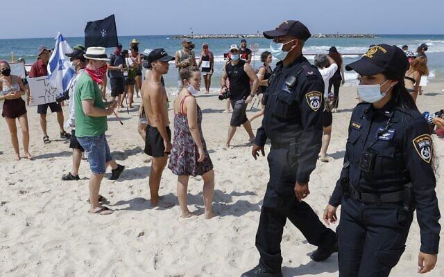 Police officers patrol on a beach as Israelis demonstrate in Tel Aviv against the nationwide coronavirus lockdown, on September 19, 2020. (Jack Guez/AFP)
