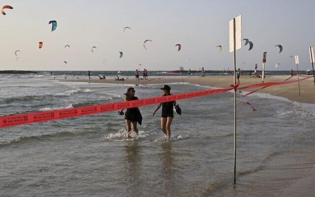Kite surfers and beachgoers are seen at a cordoned-off beach in Tel Aviv on September 19 2020, during a nationwide coronavirus lockdown. (Menahem Kahana/AFP)