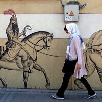 A woman, wearing a protective mask due to the COVID-19 coronavirus pandemic, walks past a graffiti depicting the legendary Persian hero Rustam (or Rostam) riding his horse behind a bound prisoner in Iran's capital Tehran on September 20, 2020. (ATTA KENARE/AFP)