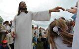 """This photo taken on August 28, 2009,  shows """"Vissarion the Teacher,"""" or """"Jesus of Siberia,"""" Russian ex-traffic cop Sergei Torop, with his followers in the remote village of Petropavlovka. (Alexander NEMENOV / AFP)"""