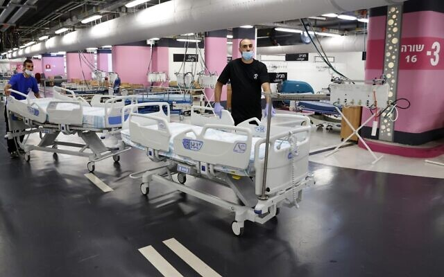 Technicians prepare beds in the underground parking of Rambam Health Care Campus which was transformed into an intensive care facility for coronavirus patients, in the northern Israeli city of Haifa on September 23, 2020.(Photo by JACK GUEZ / AFP)