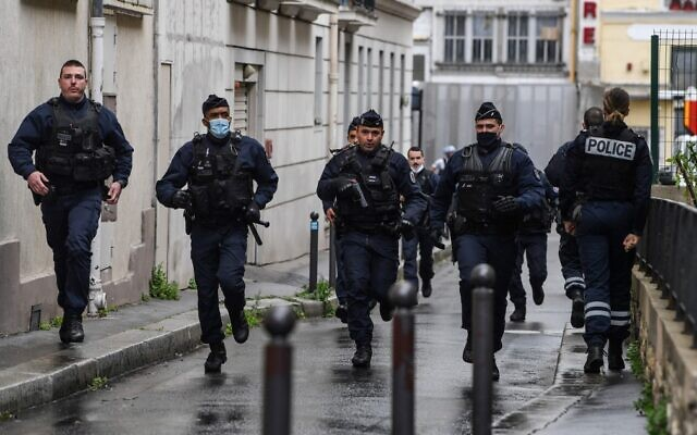 French police officers rush to the scene after people were stabbed in a suspected terror attack near the former offices of the French satirical magazine Charlie Hebdo, in Paris, on September 25, 2020. (Alain Jocard/AFP)