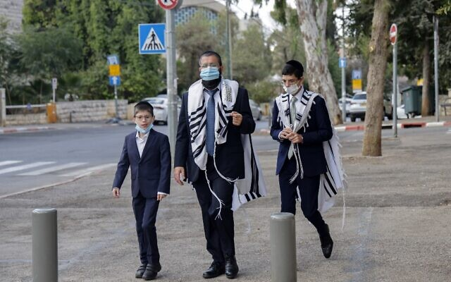 A mask-clad ultra-Orthodox Jewish man and youngsters walk along a street in Jerusalem during the second nationwide lockdown imposed by the government in a bid to stem the spread of the coronavirus COVID-19, on September 26, 2020. (MENAHEM KAHANA / AFP)