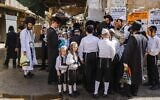 Ultra-Orthodox Jewish men and boys, a few mask-clad due to the coronavirus pandemic, stand along a street corner in the neighborhood of Mea Shearim in Jerusalem a few hours before the start of Yom Kippur, on September 27, 2020 (MENAHEM KAHANA / AFP)