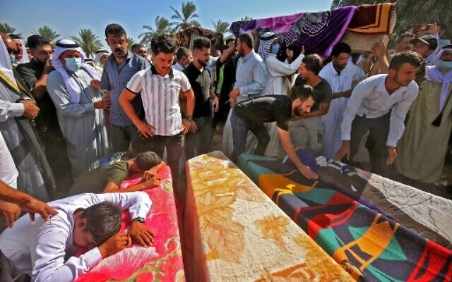 Iraqi men mourn over the coffins of members of a family who were killed a day earlier when a rocket hit their home near Baghdad's airport, during their funeral in the village of Al-Bu Shaban in the Radwaniyah area on the outskirts of the capital, on September 29, 2020 (AHMAD AL-RUBAYE / AFP)