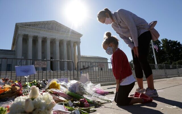Five-year-old Abby Martin of Arlington, Virginia, pays respect with her mother Jackie Martin as they visit a makeshift memorial in front of the US Supreme Court for the late Justice Ruth Bader Ginsburg September 21, 2020, in Washington, DC. (Alex Wong/Getty Images/AFP)