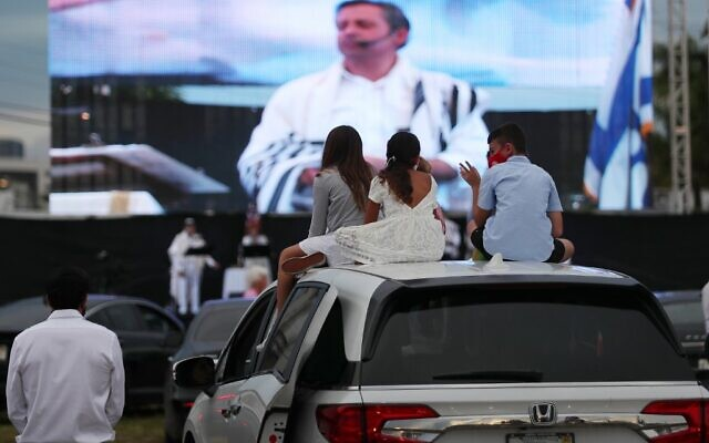Rabbi Jonathan Berkun is seen on a large screen as people watch during a drive-in Yom Kippur service put on by Aventura Turnberry Jewish Center at the Dezerland Park on September 28, 2020 in North Miami, Florida (Joe Raedle/Getty Images/AFP)