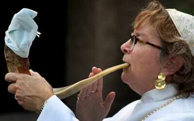 Rabbi Andrea Gouze of Easton, Massachusetts, demonstrates how she will blow the traditional shofar during the High Holidays services. The end will be covered with a face mask to prevent transmission of virus. (David L. Ryan/The Boston Globe via Getty Images via JTA)