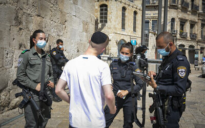 Police fine a man for violating the national lockdown rules at the Jaffa Gate in the Old City of Jerusalem on September 24, 2020. (Olivier Fitoussi/Flash90)