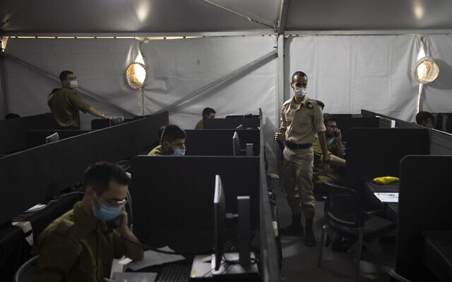 IDF soldiers interview people infected with coronavirus to identify who they have been in contact with, at the headquarters of the Home Front Command, in Ramle, August 25, 2020. (AP Photo/Sebastian Scheiner)