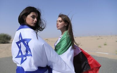 Israeli model May Tager, left, covers herself with an Israeli flag next to Anastasia Bandarenka, a Dubai-based model who covers herself in a UAE flag on the set of a photo shoot in Dubai, United Arab Emirates, Sunday, September 8, 2020. (AP Photo/Kamran Jebreili)