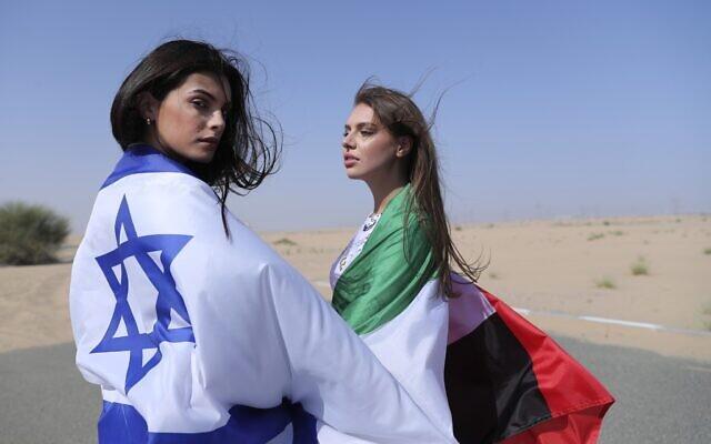 Israeli model May Tager, left, covers herself with an Israeli flag next to Anastasia Bandarenka, a Dubai-based model who covers herself in a UAE flag on the set of a photo shoot in Dubai, United Arab Emirates, Sunday, September 8, 2020. (AP Photo/Kamran Jebreili)