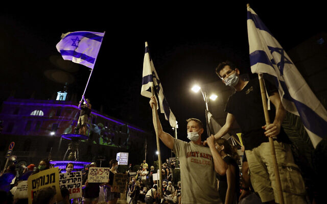 Israeli protesters wave flags during a demonstration against Israeli Prime Minister Benjamin Netanyahu outside the Prime Minister's residence in Jerusalem, Saturday, Sept. 12, 2020. (AP Photo/Sebastian Scheiner)