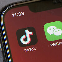 Icons for the smartphone apps TikTok and WeChat are seen on a smartphone screen in Beijing (AP Photo/Mark Schiefelbein)