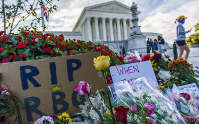 People gather at the US Supreme Court on the morning after the death of Justice Ruth Bader Ginsburg, 87, Saturday, Sept. 19, 2020 in Washington. (AP Photo/J. Scott Applewhite)