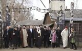 In this January 23, 2020, file photo, a delegation of Muslim religious leaders gather at the gate leading to the former Nazi death camp of Auschwitz, together with a Jewish group in what organizers called 'the most senior Islamic leadership delegation' to visit the former death camp in Oswiecim, Poland. (American Jewish Committee via AP, File)