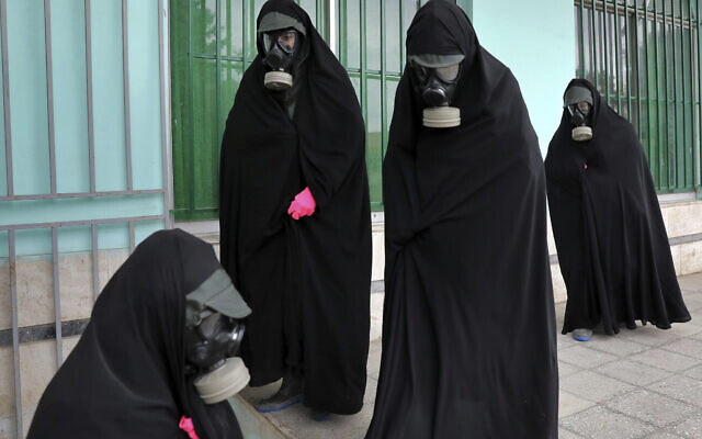 Cleric women wearing protective clothing and 'chador,' a head-to-toe garment, arrive a cemetery to prepare the body of a victim who died from the new coronavirus for a funeral, in the city of Ghaemshahr, in north of Iran, Thursday, April 30, 2020. (AP/Ebrahim Noroozi)