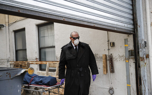 Funeral director Tom Cheeseman wears personal protective equipment due to COVID-19 concerns as he collects a body from a nursing home, Friday, April 3, 2020, in the Brooklyn borough of New York. 'We took a sworn oath to protect the dead, this is what we do,' he said. 'We're the last responders. Our job is just as important as the first responders.' (AP/John Minchillo)